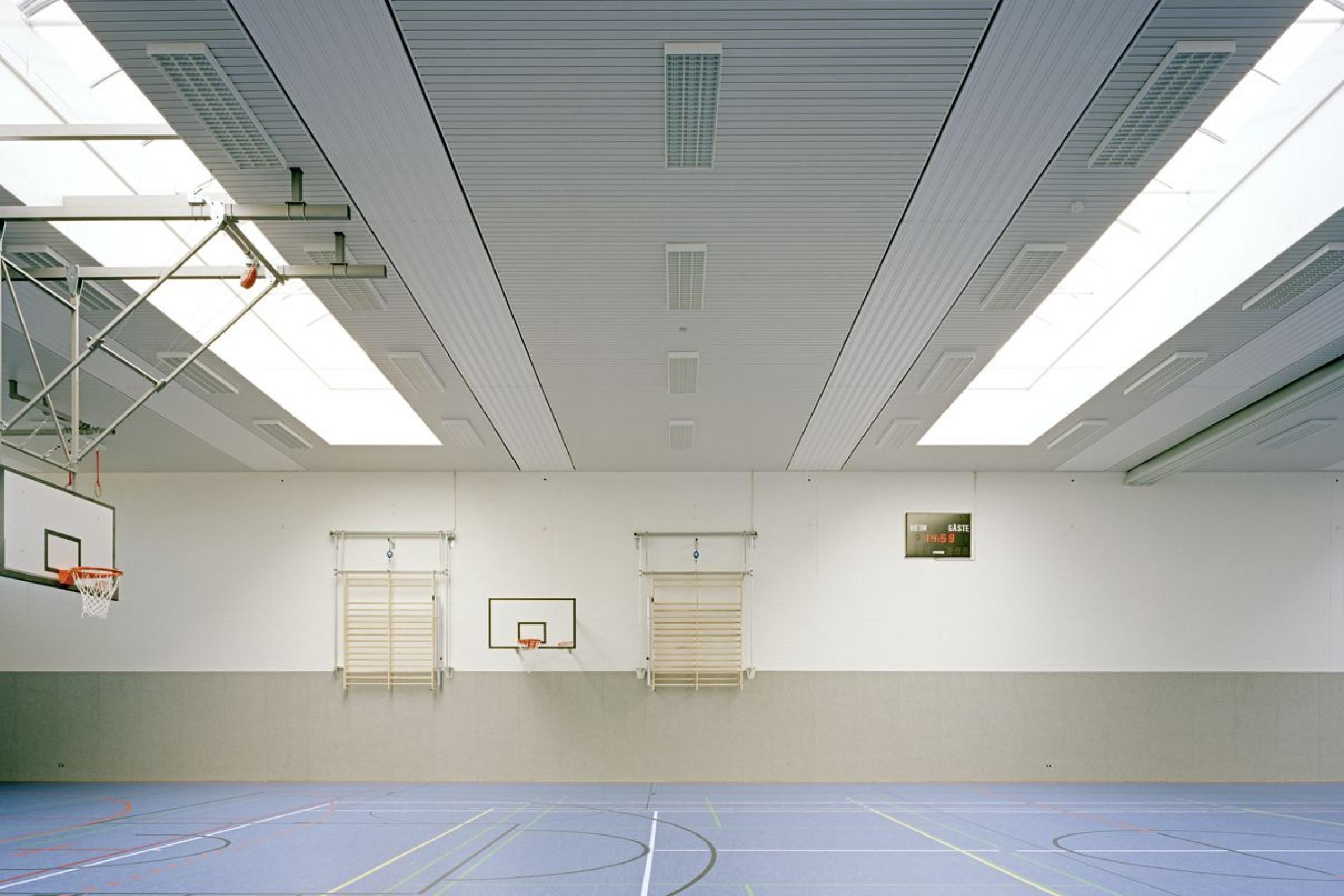 Sporthalle mit blauem Boden und Basketballkörben. An der Decke sind ballwurfsichere weiße und graue Metallpaneeele montiert.